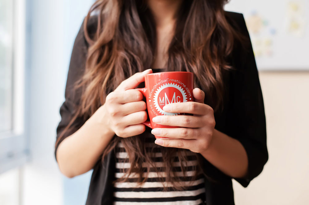 woman holding cup of coffee with MMC on it